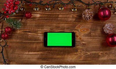 Smartphone is on the table, next to the New Year's lights. Top view