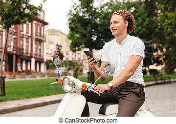 smartphone, kędzierzawy, handlowy, precz, patrząc, dzierżawa, uśmiechnięty człowiek