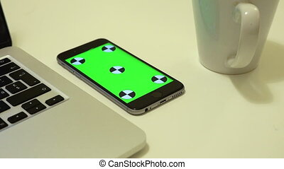 Smartphone lies on an office desk with chroma key on a screen