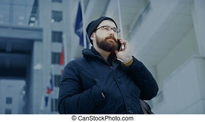 Smartphone man talking on phone in front of business center