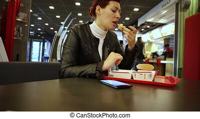 smartphone, manger, jeune regarder, hamburger, femme