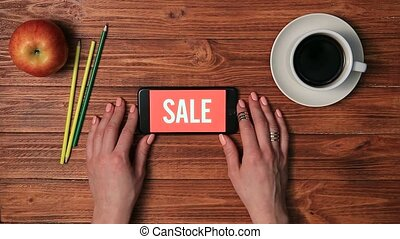 Smartphone on female hand with SALE on screen