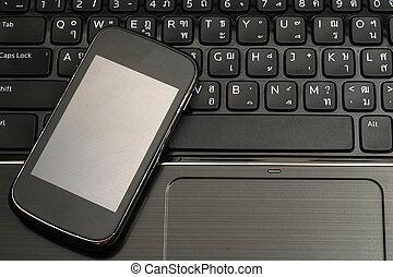 Smartphone on laptop keyboard