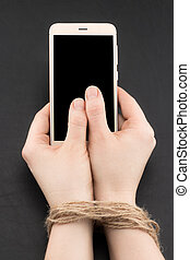 Smartphone or internet addiction with woman hands tied by twine