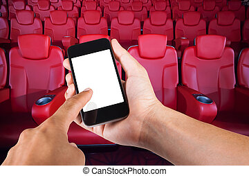 smartphone, på, hand, och, vita skärma, med, suddig fond, av, säte, in, film, theater.