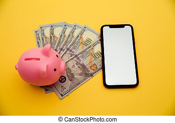 Smartphone, pink piggy bank and dollar bills on yellow background