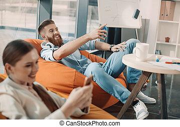 smartphone, pointage, femme affaires, loin, écouteurs, quoique, homme affaires, utilisation, sourire