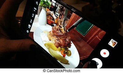 smartphone screen with a fried meat dish and some vegetables which looks delicious