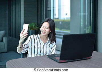 smartphone, selfie, handlowy, wpływy, przypadkowy, kobieta, asian, przód, mieszkanie, laptop
