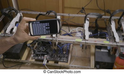 Smartphone software used for mining cryptocurrency rig held...