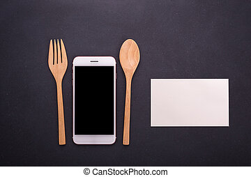Smartphone, spoon and fork on black stone table background, concept Eating technology