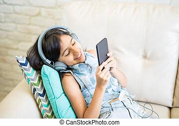 smartphone, szoba, ülés, pamlag, spanyol, zene hallgat, gyermek, otthon, mosolygós, fekvő