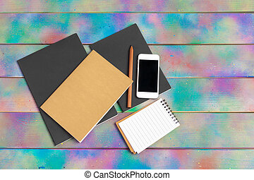 smartphone, tablet, notebook pen on the background of a wooden table