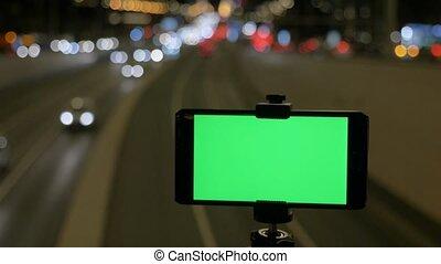 smartphone, tripod., ekran, cars., przeciw, światła, time., wieczorny, zielone tło, handel, konny