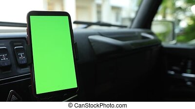 Smartphone with a green screen in the car - Smartphone with...