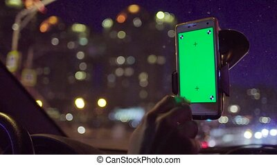 Smartphone with a green screen in the holder.