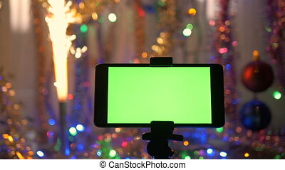 smartphone with a green screen on a new years background the festive fireworks are