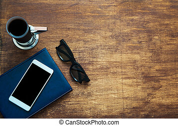 Smartphone with black blank space on the screen, blue notebook, black eyeglasses and coffee on wooden background. Top view. Copy space