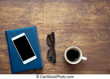 Smartphone with black blank space on the screen, blue notebook, black eyeglasses and coffee on wooden background. View from above
