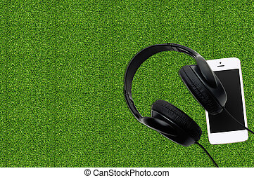 Smartphone with black earphones on the grass
