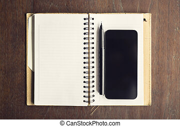 Smartphone with blank diary and pen on a wooden table