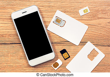 Smartphone with blank screen and SIM cards on the table, top...