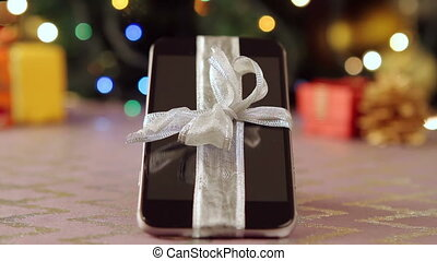 Smartphone with Christmas gifts and decorations in front of...