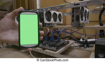 Smartphone with green screen display next to cryptocurrency...
