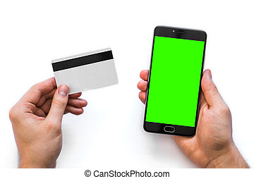 Smartphone with green screen for chroma key compositing and a credit card in the hands man white background, Internet commerce use of online banking to pay goods in Internet, top view. isolated