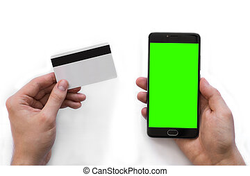 Smartphone with green screen for chroma key compositing and a credit card in the hands of a man on a white background, Internet commerce of online banking to pays in Internet, top view. isolated