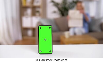 smartphone with green screen on table at home - technology...