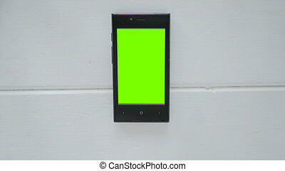Smartphone with green screen on white table