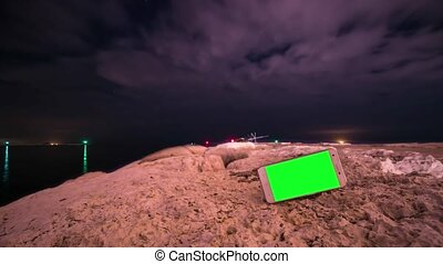 Smartphone with green screen with timelapse in the background