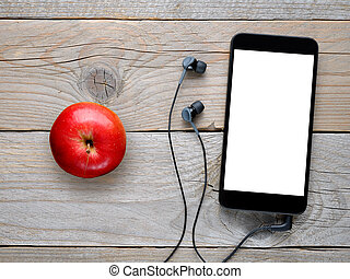 Smartphone with headphones and red apple on wooden table top...
