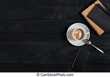Smartphone with notebook and cup of coffee on wooden background. Cell phone with writing set with espresso