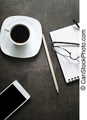Smartphone with notebook and cup of coffee on wooden background.
