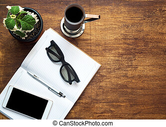 Smartphone with open notebook, black glasses and cup of coffee on wooden background. View from above. Copyspace