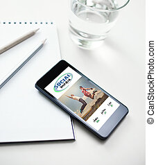 Smartphone with social media concept on screen, cup of water and