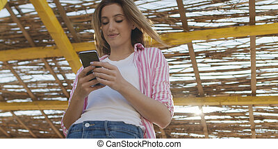 Smartphone Woman Texting On Cell Phone At Beach
