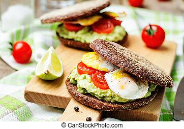 smashed avocado, tomatoes, egg sandwich. toning. selective ...