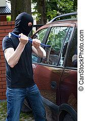 Smashing car glass - Vertical view of burglar smashing car...