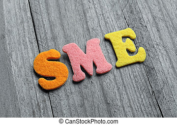SME (Small Medium Enterprises) acronym on wooden background