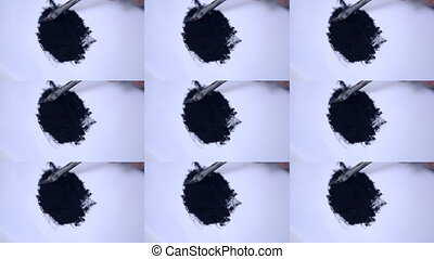 Smearing black paint with a brush on white paper.