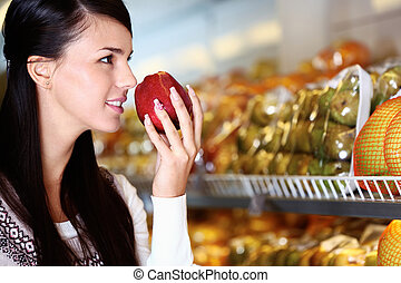 Image of young woman with fresh apple in hand smelling it in supermarket