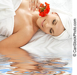 smell of red on white sand - lovely woman in spa smelling...