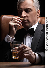 Smelling a cigar. Confident mature businessman smelling a cigar and holding a glass of whiskey in his hand