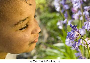 A beautiful mixed race little girl smelling bluebells