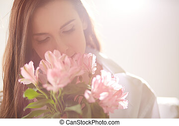 Portrait of lovely lady looking at flowers and smelling them