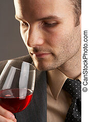 Man taking a smell at a glass of red wine