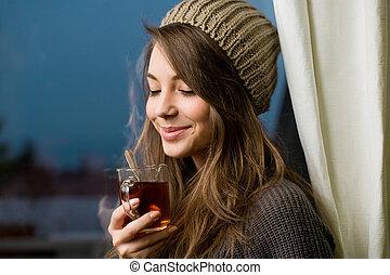 Smells great. - Portrait of a gorgeous brunette enjoying hot...